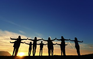 friends with arms raised at sunset enjoying moment of silence, feeling free and touching hands, silhoettes.